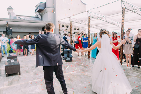 The back view of the dancing newlywed couple in the rain of confetti.