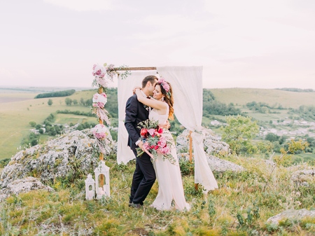 The newlywed couple is hugging near the wedding arch in the mountains. The horizontal outdoor photo. Stok Fotoğraf