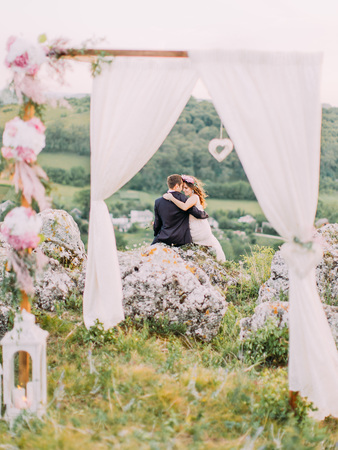 The back view of the cheerful newlyweds sitting on the huge rock in the front of arch. Stok Fotoğraf