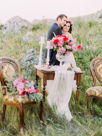 The vertical view of the hugging newlyweds behind the blurred wedding table set.