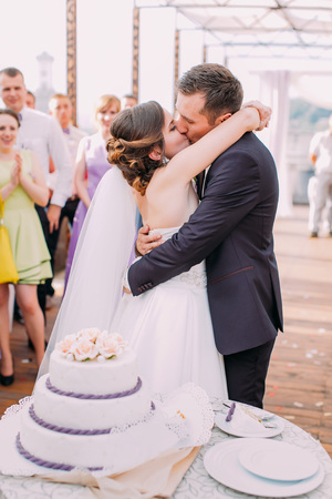 Cheerful kissing newlywed couple behind the wedding cake. 스톡 콘텐츠