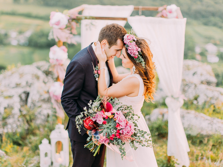 The hugging newlyweds standing nose-to-nose at the background of the wedding arch in the mountains. Stok Fotoğraf