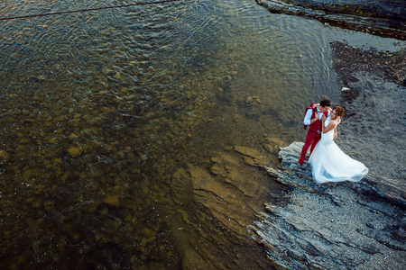 Cheerful stylish newlywed couple is hugging on the river bank during the sunny day. Above view.