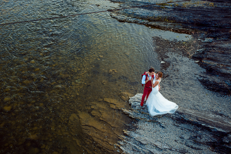 Romantic above portrait of the smiling newlyweds tenderly hugging at the river bank during the sunny day.