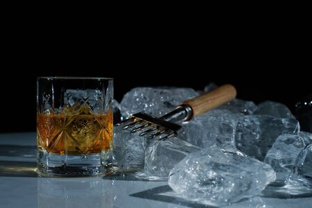 close up photo of equipment for the bar. Special knife for chopping ice, glass of whiskey, ice