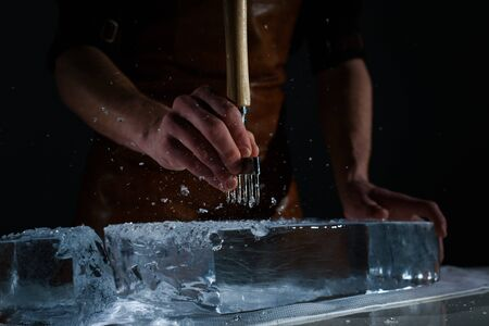 Bartender chopping ice using a special knife. Peaces of ice goes around Standard-Bild - 140240869