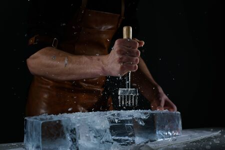 Bartender chopping ice using a special knife. ?hunks of ice flying around
