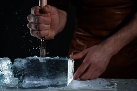 Barman chopping ice using a special knife. Ð¡hunks of ice flying around Banque d'images - 140240866