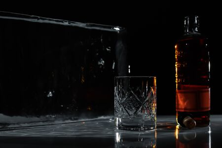 ice, empty glass, bottle of whiskey, cork on the black table Banque d'images - 138577019