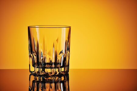 Empty glass against yellow background Banque d'images