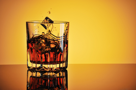 Glass of whisky with ice against yellow background photo