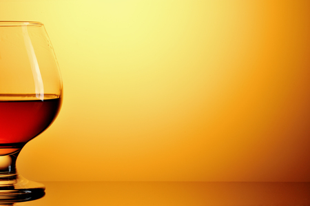 Glass of cognac on yellow background Stock Photo