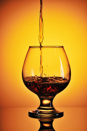 Pouring cognac in glass on a gold background