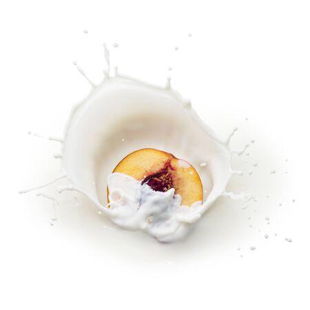 Fresh yellow peach half falling into milk with splash