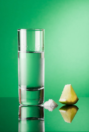 Tequila in a glass with a slice of lemon on green background