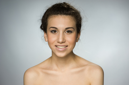 Beautiful brown-eyed natural girl on gray background Stock Photo