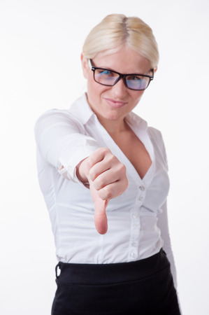 Pretty business woman wearing glasses with thumb down on a white background