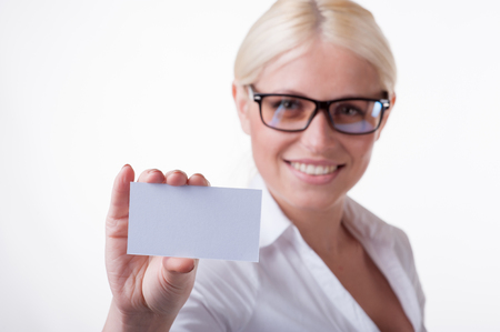 Happy blond woman showing blank business card Stock Photo