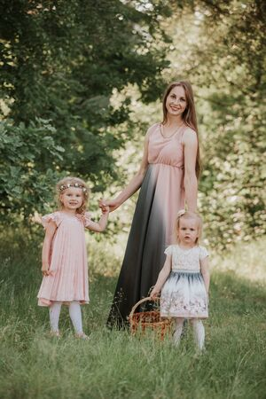 Mother and two daughters whirling. Mother holds daughters on hands. Family time together. a wonderful portrait of mom with two daughters in the park Stock Photo