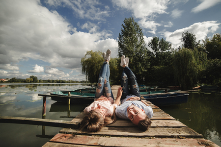 Beautiful young couple and smiling while lying on the pier. happy young man and woman laughing while lying on wooden pier near water