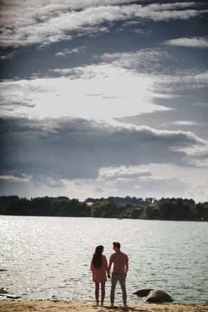 lovely couple stands by the water along river shore, holding hands together, happy family concept. love story.