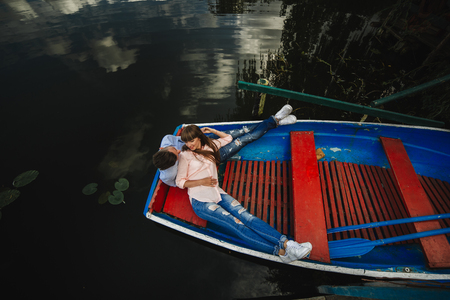 Loving couple in boat. Top view of beautiful young couple embracing and smiling while lying in the boat