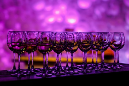 Stemware in purple light. Many glass of wine on a table. Glasses with wine. Filled with half and stand on the holiday table. Furshet. selective focus Imagens