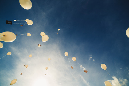 White balloons fly up into the blue sky. The release of festive balloons in the clouds. Celebration and happiness. Air gel balls in the atmosphere.