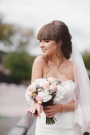 Hochzeitsmodebraut mit Blumenstrauß in den Händen. Junge schöne Braut in einem eleganten Kleid mit einem Blumenstrauß bei der Hochzeitszeremonie