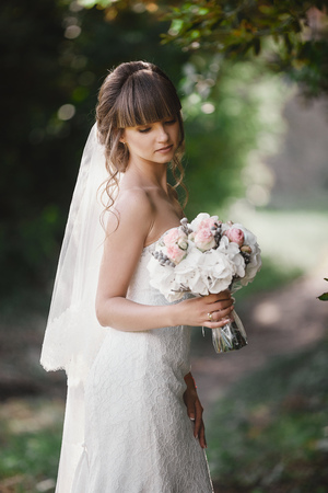 Beautiful young smiling bride holds large wedding bouquet with pink roses. Wedding in rosy and green tones. wedding day