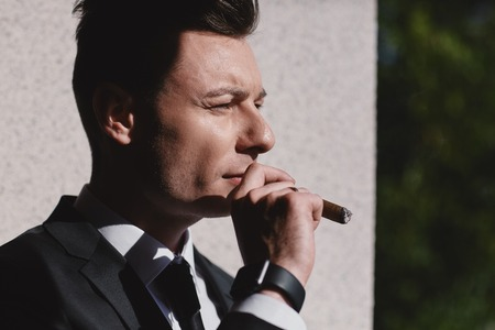 Cropped portrait of hard gaze businessman while smoking a cuba cigar.