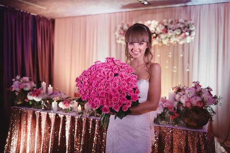 happy bride with a large bouquet of roses. beautiful young smiling bride holds large wedding bouquet with pink roses. Wedding in rosy and green tones. Rain at the wedding ceremony.