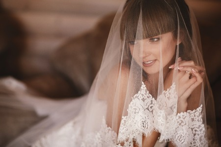 Portrait of charming bride sitting on the bed in a hotel room. the bride is covered with veil. Close up. Wedding morning. Gentle, Tender emotion on the face Imagens