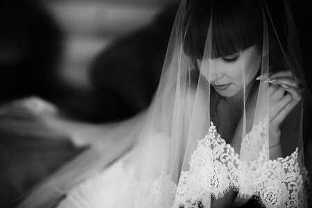 Portrait of charming bride enveloped in a veil. Black and white picture of beuatiful bride hidden under the veil. Close up. Wedding morning
