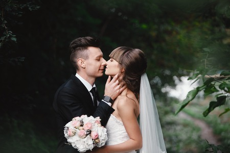 Bride and groom in a park kissing. couple newlyweds bride and groom at a wedding in nature green forest are kissing photo portrait.Wedding Couple. Newlyweds Imagens
