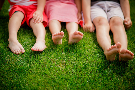 legs on the grass. bare legs of little girls sitting on the meadow. Selective focus, children sit on the grass with bare legs