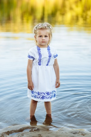portrait of a little girl who stands in water in a white dress. beach in summer