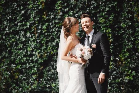 Retrato de detalle de la novia y el novio de la boda con ramo posando junto a la catedral vieja. Pareja nupcial, mujer recién casada feliz y hombre abrazándose. La novia y el novio Foto de archivo