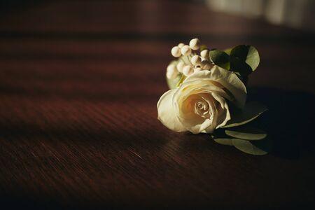 Die Braut, die in der Handnahaufnahme die Knopflochblumen des Bräutigams mit weißen Rosen und Grün und Grün hält. Vorbereitungen der Braut. Hochzeitsmorgen-Konzept.