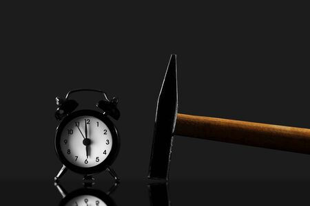 wake up with a hammer on a black background. Black old style alarm clock isolated