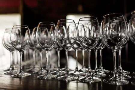 empty wine glasses. Beautiful new glasses for wine from glass stand in even rows on a wooden table in a restaurant. selective focus