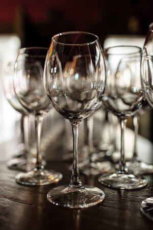 leere Weingläser. Schöne neue Gläser für Wein aus Glas stehen in gleichmäßigen Reihen auf einem Holztisch in einem Restaurant. selektiver Fokus