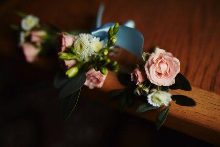 Stilvolles Knopfloch, Ansteckblume für den Bräutigam. Hochzeitszubehör auf dem Tisch auf Holzuntergrund. Flach liegen. Ansicht von oben