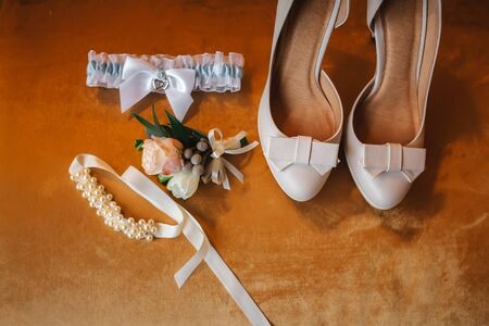 Wedding accessory bride. Stylish beige shoes, buttonhole and garter on wooden background