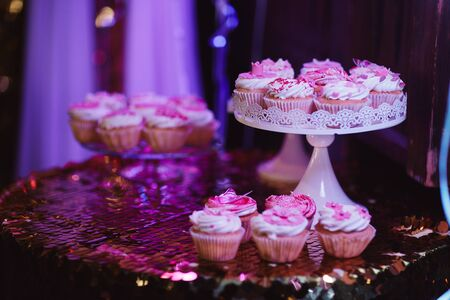 Set of different delicious tasty muffins on table festive background with shiny pink tablecloth. Different dessert tartlets with decorated cream and pink scenery . Selective focus. Candy bar concept