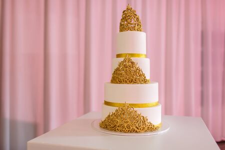 wedding cake with gold. Wedding cake, on white table. 3-tiers covered in ivory fondant sprayed with pearl spray and yellow roses made of sugar paste.