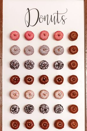wedding chocolate donuts for guests. festive concept. sweets on a wedding day. wedding donuts. A yummy donut wall
