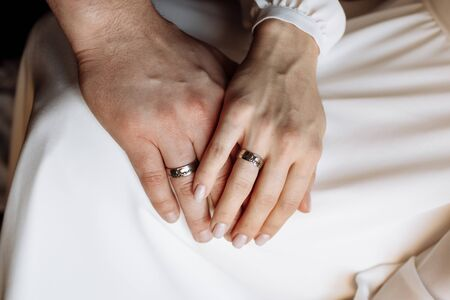 Hands of the bride and groom with gold wedding rings. Wedding concept