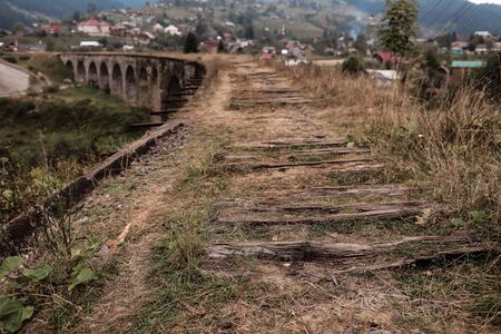 Close view of old railroad tracks with worn ties. Railway viaduct Ukraine, Verkhovyna.