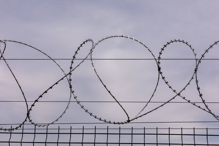 Barbed wire against the cloudy sky. Barbed wire fencing from the prison fence. The concept of captivity, slavery, prisoners, convicted. Prison, checkpoint, security territory, border, military base.